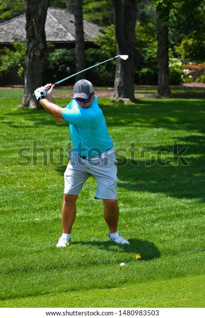 Young Man Swinging a Golf Club to Hit a Golf Ball Down the Fairway