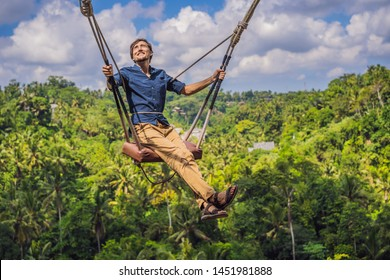 Young man swinging in the jungle rainforest of Bali island, Indonesia. Swing in the tropics. Swings - trend of Bali