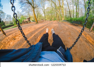 young man swinging on a playground, point of view perspective