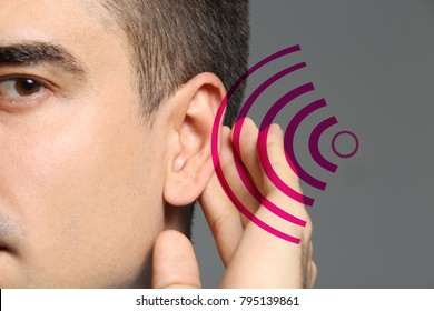 Young man with symptom of hearing loss on color background