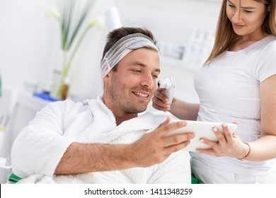 Young man with tablet in cosmetic salon checking condition of his skin