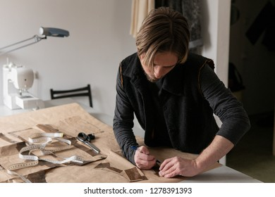 Young man tailor making clothing pattern while work in workshop