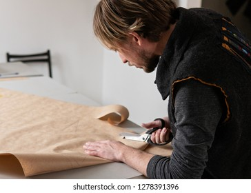 Young man tailor with scissors making clothing pattern while working in workshop