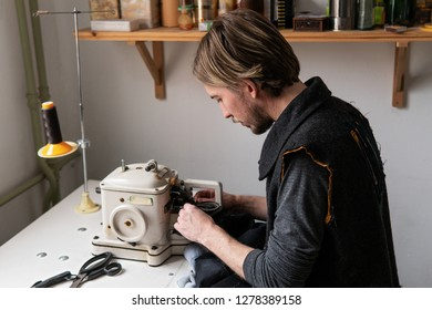 Young man tailor working on furrier machine in workshop