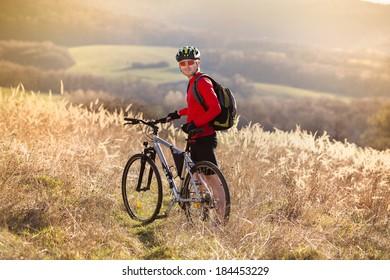 Young man takes a break in a field while mountain biking