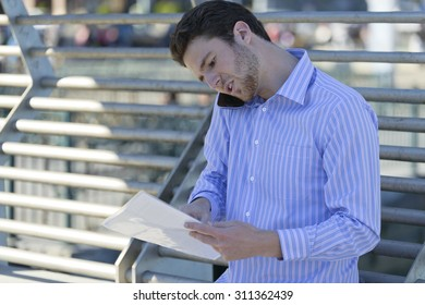 Young man takes a business call outdoors