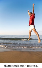 Young man takes a great leap on a beach at sunrise: happiness, fitness, success concept
