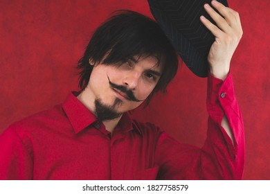Young man takes off his hat. male portrait on the red background