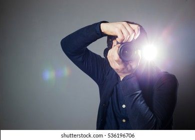Young man takes a picture on a camera with built-in flash. Bright light for illumination of the frame.