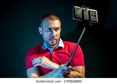 A young man takes a selfie on a dark green background