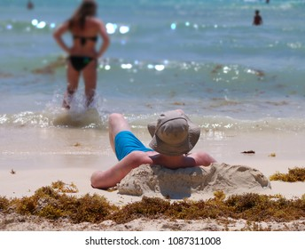 Young man takes a sunbath on a beach.