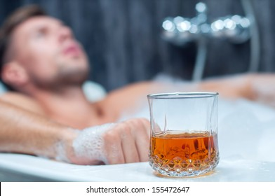 young man taking a bath, drinking whiskey
