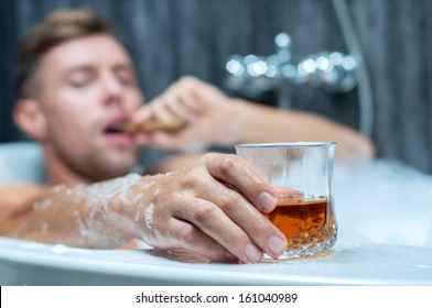 young man taking a bath, drinking whiskey and smoking cigar