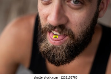 Young man taking LSD; LSD card on a man's tongue. Focus on the LSD stamp