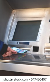 Young man taking money from account from atm