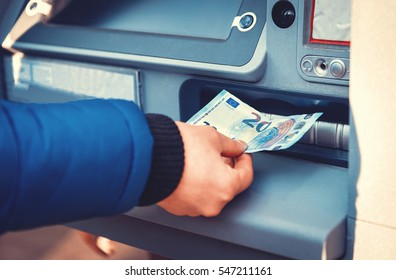 Young man taking money from your account from atm