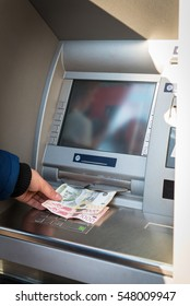 Young man taking money from your account in atm