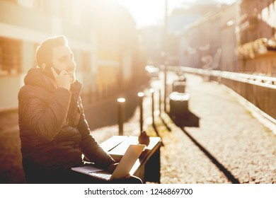 young man, taking phone calls and working from urban alley during autumn