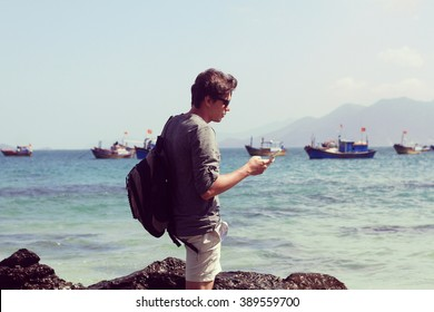 young man taking photo by his phone on the beach on stones with sea view