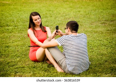 Young man taking photo of her girlfriend with mobile phone in nature