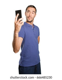 Young man taking a photo with his mobile phone on white background