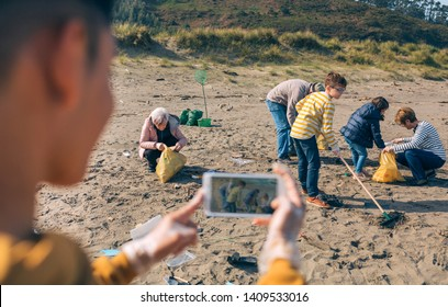 Young man taking photo with mobile to group of volunteers cleaning the beach. Selective focus on group of people in background