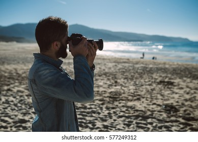 Young man taking a photo on the beach in a sunny morning