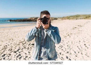 Young man taking a photo with a reflez camera on the beach