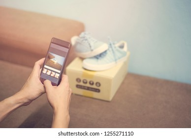 young man taking photo sneakers with camera smartphone for post to sell online on the internet market website / selling online ecommerce shipping online shopping delivery and order concept