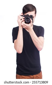 Young man taking picture with film camera isolated