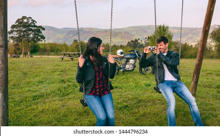 Young man taking a picture of his girlfriend sitting on the swings in a recreational area