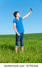 young man taking picture on phone against green grass and blue sky