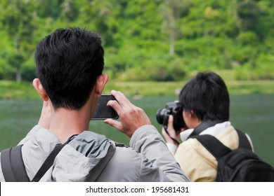 young man taking picture of a woman while taking picture of nature with digital camera