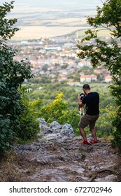 Young man taking pictures of a city with a DSLR on a tripod