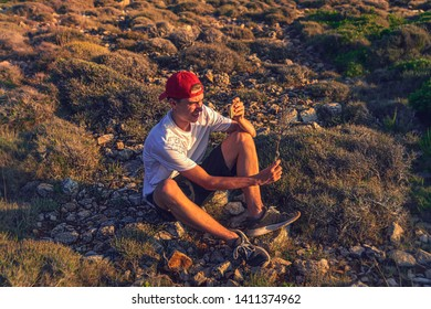 young man taking pictures with a phone, sitting on the ground