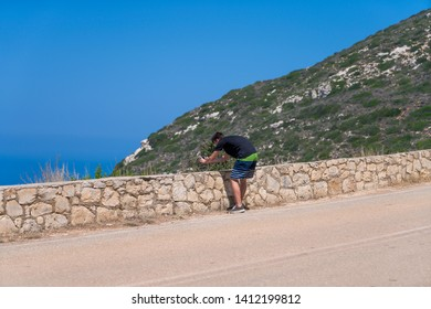 young man taking pictures with a phone in mediterranean landscape