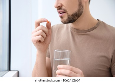 Young man taking pill indoors
