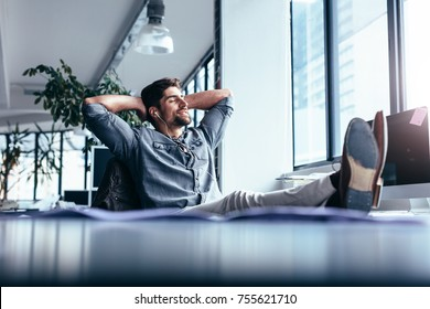 Young man taking rest and listening music while sitting in office. Male designer sitting relaxed at his workplace.