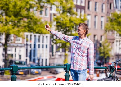 Young man taking self portrait in european city outdoors. Young adult holding smartphone camera to take a picture of herself during her summer vacation in Amsterdam