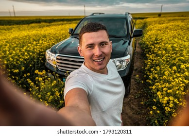 young man taking a selfie in front of a offroad car in blooming rape field