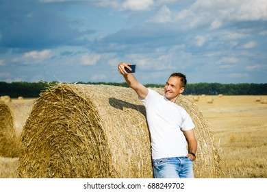 Young man taking selfie from mobile phone while standing on field