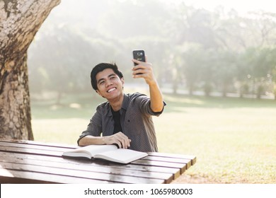 Young man taking selfie at a park