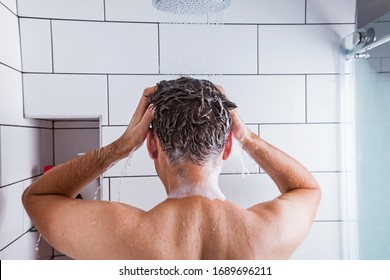 Young man taking a shower and washing his hair, view from the back