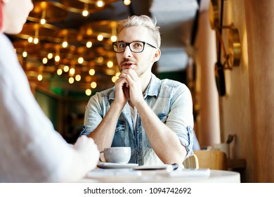 Young man talking to his unrecognizable female friend in cafe. Guy telling story or giving interview over cup of coffee.