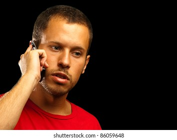 young man talking with the mobile phone on black background