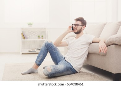 Young man talking on mobile at home. Boy in glasses sitting on the floor having an unpleasant conversation, copy space