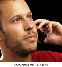 young man talking on mobile phone on black background