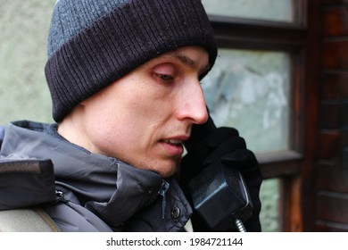 A young man is talking on Payphone