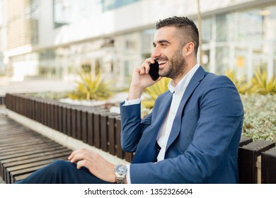 Young man talking on the phone outside and smiling