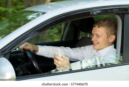 Young man talking on the phone behind the wheel of a car, creating an emergency situation
